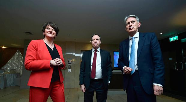 Arlene Foster and Nigel Dodds meet Chancellor Phillip Hammond as he arrives to speak at the DUP party conference. (Photo by Charles McQuillan/Getty Images)