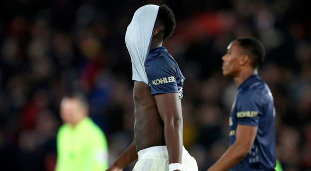 Manchester United's Paul Pogba leaves the pitch with his shirt over his head.