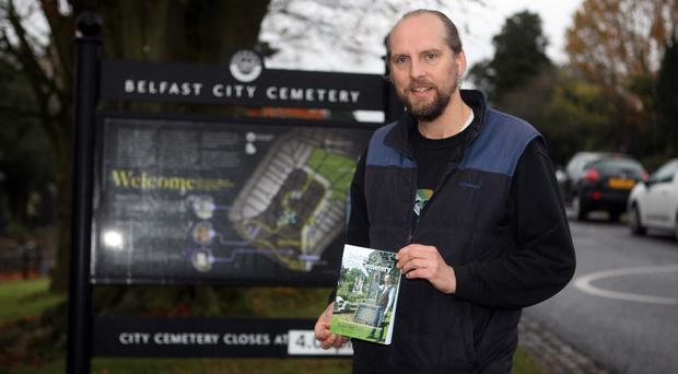 Peter McCabe with his book on the Belfast City Cemetery