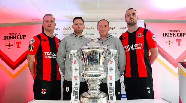 Up for the cup: Glentoran duo Ross Redman and James McFerran pose with Crusaders' Jordan and Kyle Owens and the Irish Cup after the two sides were paired together in the fifth round draw