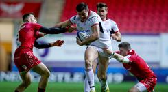 Ulster's Jacob Stockdale runs in a try despite Gareth Davies and Steff Evans of the Scarlets Credit ©INPHO/Tommy Dickson