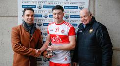 Top man: Derry's Ben McCarron accepts his man of the match trophy from Colm Moane of Bank of Ireland as Brian Armitage of the Ulster GAA looks on