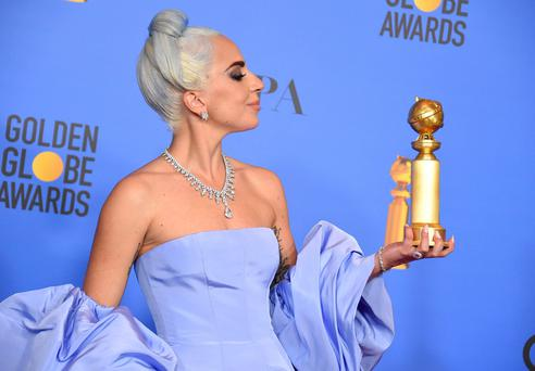 Lady Gaga poses in the press room with the award for best original song, motion picture for