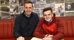 Ronan Hale puts pen to paper on a 2.5 year deal, watched by Crusaders boss Stephen Baxter.