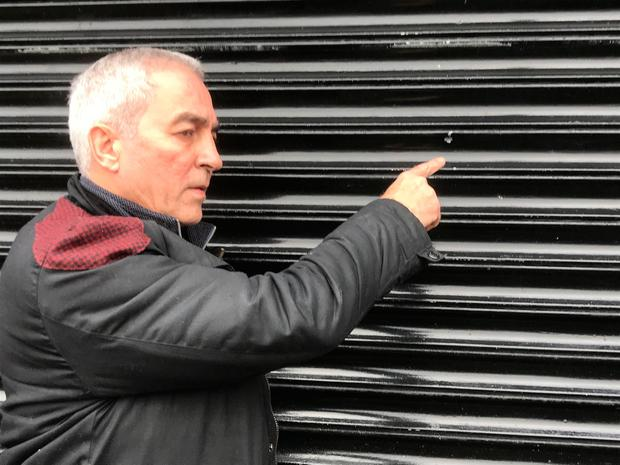 Sinn Fein MLA Pat Sheehan points to a mark made by a bullet during a gun attack on their constituency office earlier this month. Photo credit: Rebecca Black/PA Wire