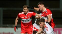 Fiery: Derry's Ramon McGill and Tyrone's Brian Kennedy in last month's McKenna Cup showdown