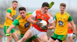 Holding on: Armagh's Rory Grugan is challenged by Brendan McCole