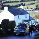 The hearse carrying the coffin of Sean Byrne makes its way from the family home to the Church of St. Malachy, Carrickcruppen, Camlough. The keen walker died on the Sunday while out walking in the Mourne mountains. Pic by Peter Morrison