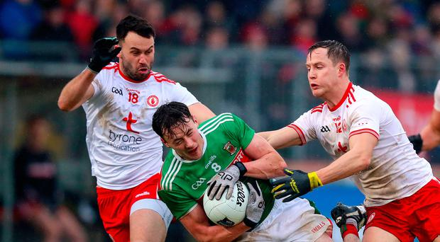 Pressure on: Mayo's Diarmuid O'Connor is closed down by Kyle Coney and Kieran McGeary