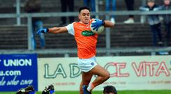 In the way: Armagh's Jemar Hall leaps over Clare defender Gordon Kelly at Pairc Esler, Newry