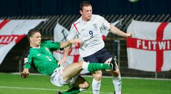 History maker: Chris Baird tackles England ace Wayne Rooney in September, 2005 when David Healy's strike sealed a famous 1-0 win