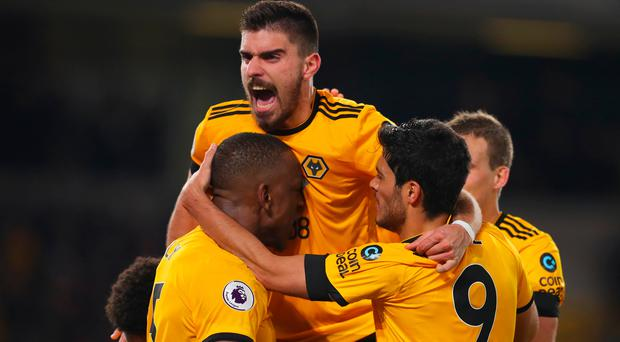WOLVERHAMPTON, ENGLAND - FEBRUARY 11: Willy Boly of Wolverhampton Wanderers celebrates with Ruben Neves (top) and team mates as he scores his team's first goal during the Premier League match between Wolverhampton Wanderers and Newcastle United at Molineux on February 11, 2019 in Wolverhampton, United Kingdom. (Photo by Catherine Ivill/Getty Images)