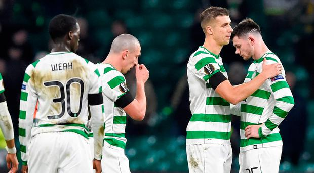 Bleak outlook: Celtic's Jozo Simunovic consoles team-mate Oliver Burke as captain Scott Brown andvTimothy Weah show their dejection after the 2-0vloss to Valencia