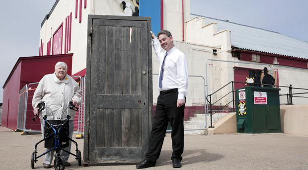 Cinema manager Neil Bates and Joyce Dowding with the door that inspired Larry Grayson's famous catchphrase 'Shut that door' at the Regent Cinema in Redcar (Stuart Boulton/PA)
