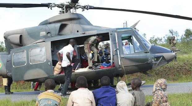 Soldiers and paramedics carry injured survivors from a helicopter in Chimanimani (TTsvangirayi Mukwazhi/AP)