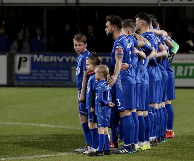 Dungannon's players stand in respect of three local teenagers who died at an incident in Cookstown on St Patrick's night. Photo by David Maginnis/Pacemaker Press