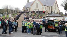 Team-mates of Connor Currie perform a huddle beside his coffin at St Malachy's Church, Edendork