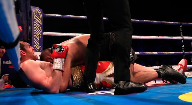 Sour taste: Kash Ali bites David Price after they fell to the canvas during their heavyweight bout in Liverpool