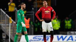 Mixed emotions: Chris Smalling, whose own goal sealed victory for Wolves, and United keeper David de Gea (left) show their agony