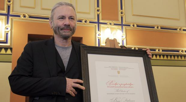 Bruce Dickinson with his honorary citizen certificate at the city hall in Sarajevo, Bosnia-Herzegovina (Eldar Emric/AP)