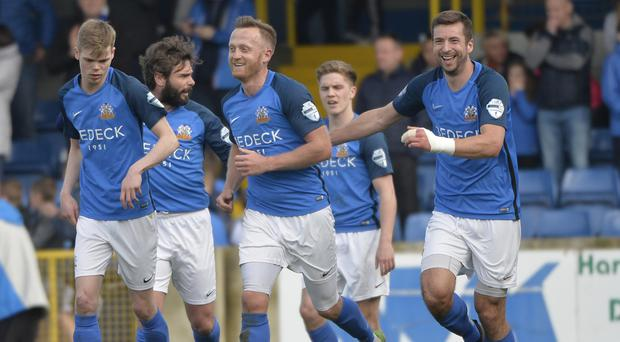 Glenavon's Sammy Clingan celebrates his late penalty winner in between the two super-subs Gary Hamilton and Stephen Murray.