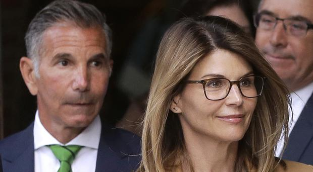 Actress Lori Loughlin, front, and husband, clothing designer Mossimo Giannulli, left, depart federal court in Boston (Steven Senne/AP)