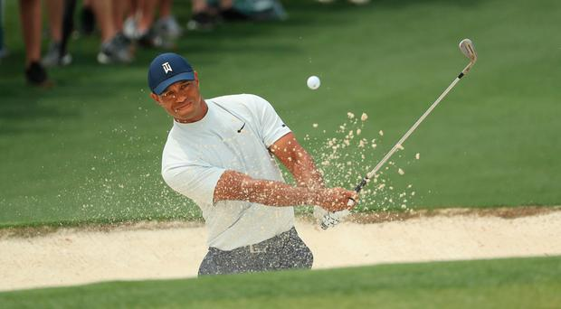 No bother: Tiger Woods plays out of a bunker on the second at Augusta