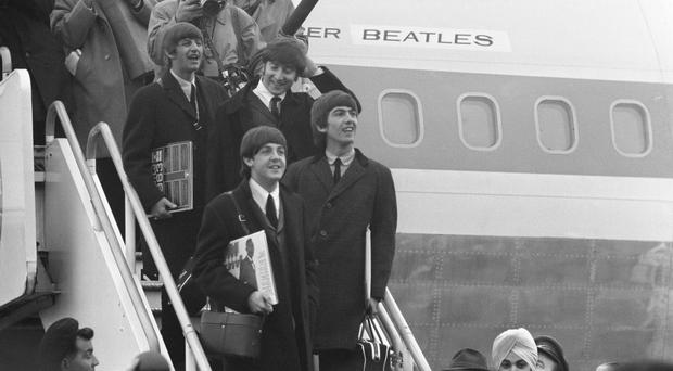 The Beatles pause to look at the huge crowds after their return from the US in 1964 (PA)