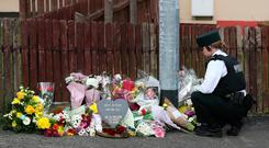 Police officer looks at flowers left at the scene where 29-year-old journalist Lyra McKee was shot on Thursday night