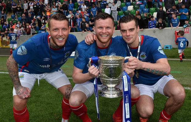 Linfield's Kirk Millar, Niall Quinn and Matthew Clarke celebrate with the Gibson Cup at Windsor Park.