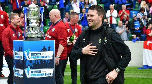Linfield boss David Healy walks past the Gibson Cup to pick up his winners' medal.