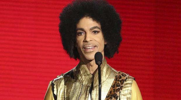 """FILE – In this Nov. 22, 2015, file photo, Prince presents the award for favorite album – Soul/RandB at the American Music Awards in Los Angeles. The memoir Prince was working on at the time of his death, """"The Beautiful Ones,"""" is due out in late October 2019. (Photo by Matt Sayles/Invision/AP, File)"""