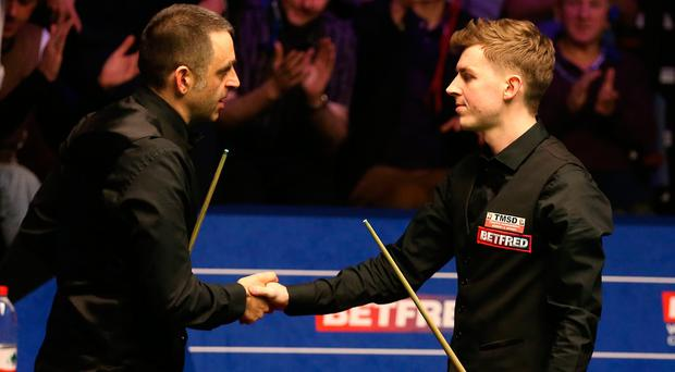 James Cahill (right) is congratulated by Ronnie O'Sullivan after his first round victory at the 2019 Betfred World Championship.