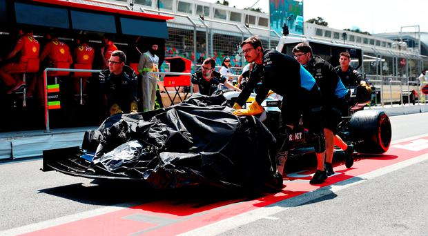Smashed up: The broken car of George Russell and Williams is pushed down the pitlane in Azerbaijan