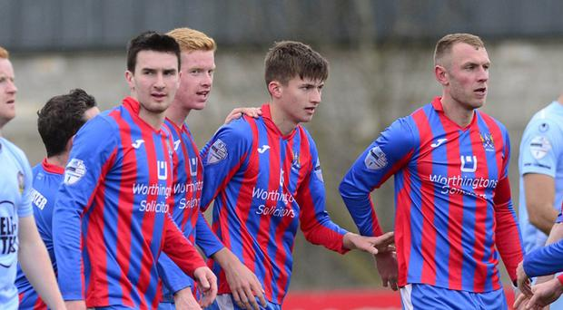 Ard's Jonah Heron is mobbed by team-mates after scoring on his debut against Warrenpoint Town.