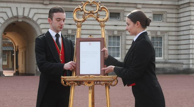 Footmen Stephen Kelly and Sarah Thompson with the formal notice on the forecourt of Buckingham Palace (Yui Mok/PA)