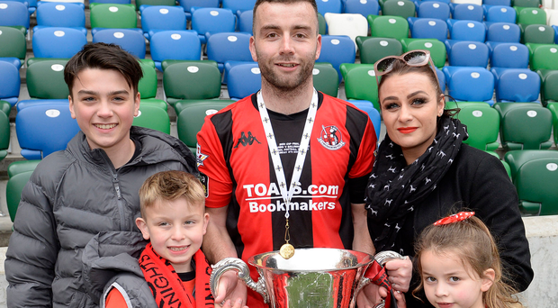 Family fortunes: Colin Coates shows off the Irish Cup with partner Claire, Zach, Rowan and Clara