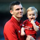 Child's play: Andy Robertson and son Rocco soak up the Anfield atmosphere after Liverpool's last game of the league campaign