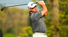 Graeme McDowell plays a shot from the second tee (Photo by Mike Ehrmann/Getty Images)