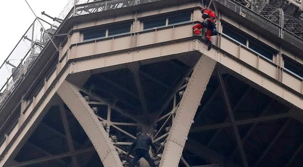 A rescue worker, top in red, hangs from the Eiffel Tower while a climber is seen below him between two iron columns Monday, May 20, 2019 in Paris. The Eiffel Tower has been closed to visitors after a person has tried to scale it. (AP Photo/Michel Euler)