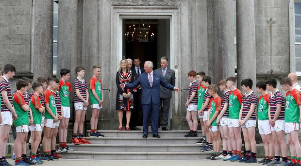 The Prince of Wales is pictured at the Palace Demesne, Armagh during his two day visit to Northern Ireland. The rugby and GAA players present HRH with two shirts as he left the Palace.