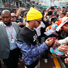 Main attraction: Lewis Hamilton signs autographs for fans in the pitlane in Monaco