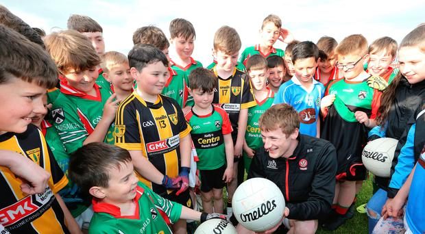 Derry GAA star Brendan Rogers is mobbed in a huddle as the senior team take to the pitch at Sean Dolans in the Creggan