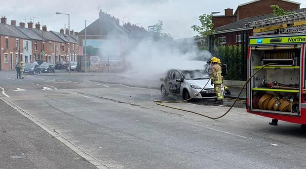Firefighters dealing with the burning car on Beechmount Avenue in Belfast. Credit: Ciaran Beattie.