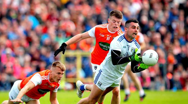 Fall guy: Armagh's Rian O'Neill and Aidan Nugent pursue Raymond Galligan