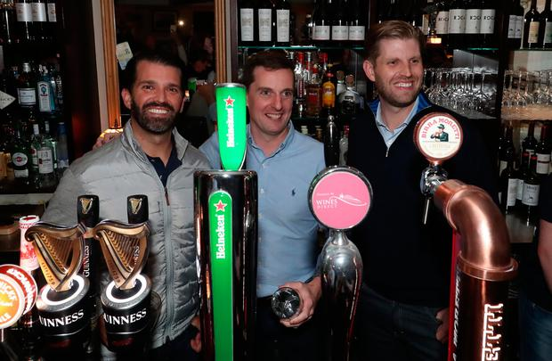 Donald Trump Jr. (left), and Eric Trump (right), the sons of US President Donald Trump, pour drinks and meet locals in the village of Doonbeg in Co Clare. Pic: Niall Carson/PA Wire