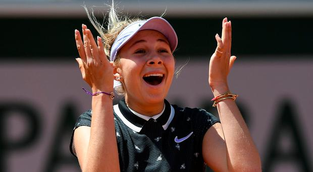 In shock: Amanda Anisimova celebrates after knocking out defending French Open champion Simona Halep