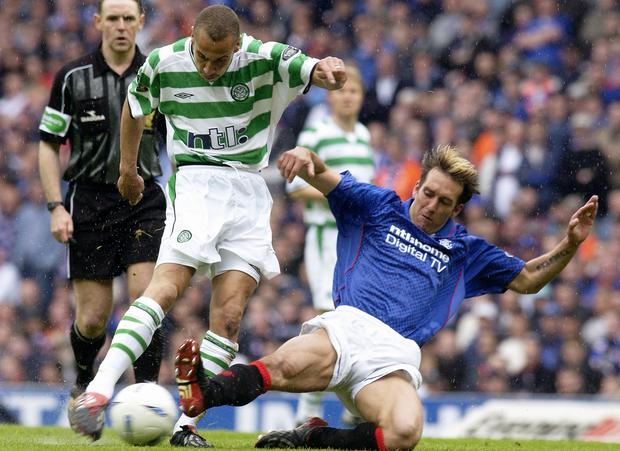 Fernando Ricksen tackles Celtic's Henrik Larsson during an Old Firm game.
