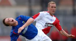 Stuck in: Rangers ace Fernando Ricksen tackles Linfield's Jamie Mulgrew in Belfast in 2006