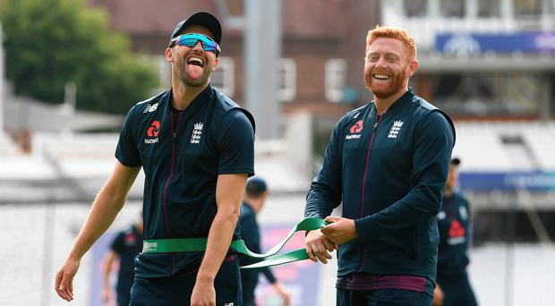 All smiles: Mark Wood shares a joke with Jonny Bairstow